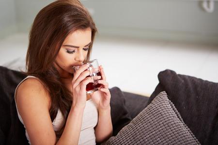 ojos verdes: Retrato del t� de consumici�n de la mujer joven en su casa sentado en el sof�.