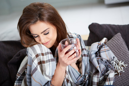 A young woman caught a cold covered with woolen plaid blanket photo