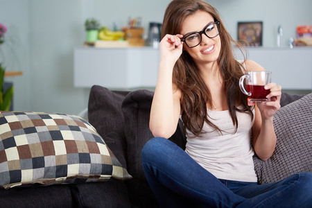 girl sit: Portrait of young woman drinking tea at home sitting on sofa.