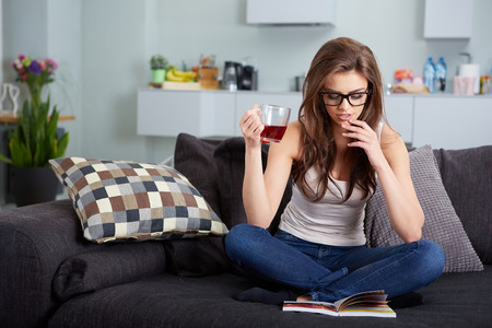 leasure: leasure and home concept - calm teenage girl woman reading book and sitting on couch at home Stock Photo