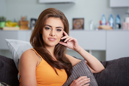 1 woman only: Portrait of relaxing attractive woman sitting on sofa