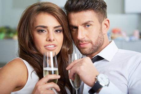 caras emociones: a young couple with champagne glasses celebrating Foto de archivo