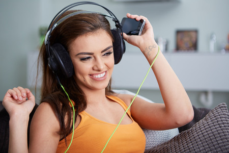 domiciles: Cute smiling woman lying on couch while listening to music in bright living room Stock Photo