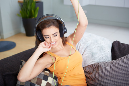 t off: Cute smiling woman lying on couch while listening to music in bright living room Stock Photo