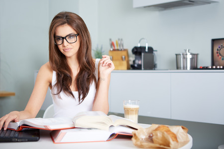 self study: a happy young woman studying in kitchen Stock Photo