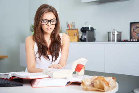 erudition: a happy young woman studying in kitchen Stock Photo