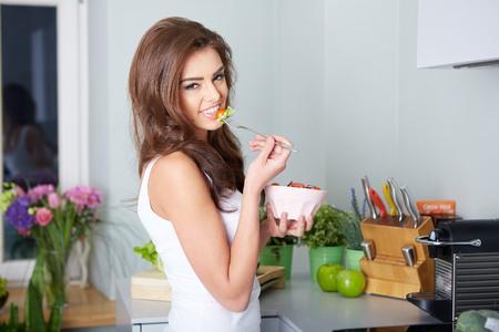 habitos saludables: mujer está comiendo un salat en un tazón, de interior Foto de archivo
