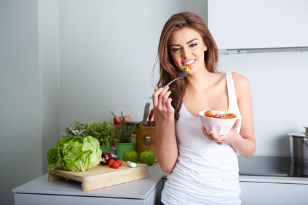 unhealthy living: woman is eating a salat in bowl, indoor