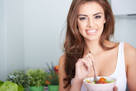 woman is eating a salat in bowl, indoor