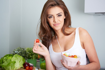 weight room: woman is eating a salat in bowl, indoor