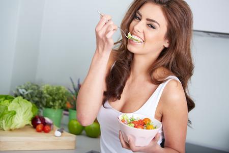 Hábitos saludables: mujer está comiendo un salat en un tazón, de interior Foto de archivo