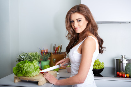 young add: a happy woman cooking a meal in the kitchen. Stock Photo