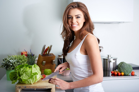 a happy woman cooking a meal in the kitchen. Stock Photo