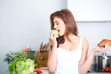 Diet. Diät-Konzept. Gesunde Nahrung. Schöne junge Frau, die zwischen Obst und Süßigkeiten