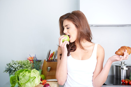 unhealthy diet: Diet. Dieting concept. Healthy Food. Beautiful Young Woman choosing between Fruits and Sweets