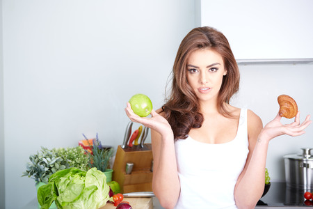 temptation: Diet. Dieting concept. Healthy Food. Beautiful Young Woman choosing between Fruits and Sweets