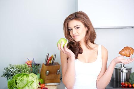 ダイエット。ダイエットのコンセプトです。健康食品。美しい若い女性は、果物やお菓子の間の選択 写真素材