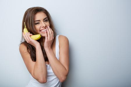 a woman making fun with a banana
