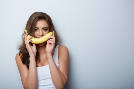 banana skin: a woman making fun with a banana