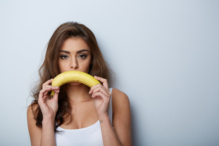 a woman making fun with a banana