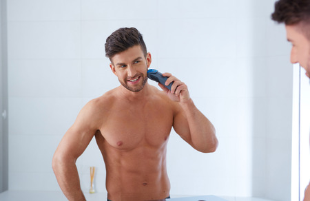 naturally: Close up portrait of young handsome man with perfect skin and hair. Shaving by electric shaver Stock Photo