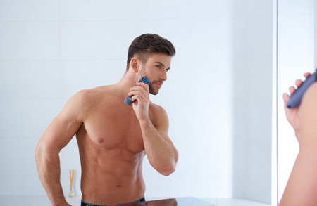 electric razor: Close up portrait of young handsome man with perfect skin and hair. Shaving by electric shaver Stock Photo