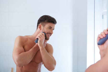 adult boys: Close up portrait of young handsome man with perfect skin and hair. Shaving by electric shaver Stock Photo