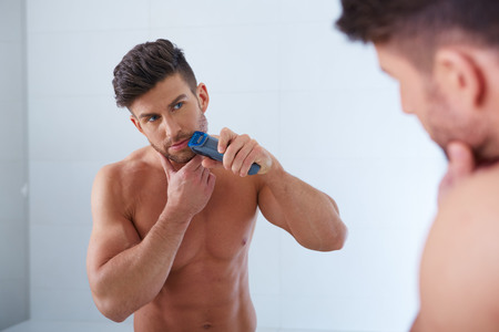 shaver: Close up portrait of young handsome man with perfect skin and hair. Shaving by electric shaver Stock Photo