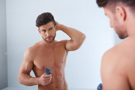Close up portrait of young handsome man with perfect skin and hair. Shaving by electric shaver Stock Photo