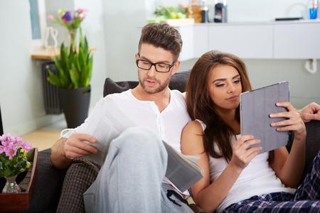 신문 읽기 뉴스와 태블릿와 남편을 가진 여자 스톡 콘텐츠
