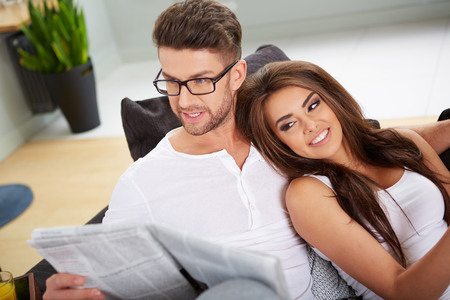 reading news: Woman with tablet and husband with newspaper reading news