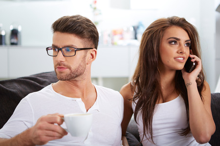 White Sitting Couple in Casual Clothing Having Coffee, with mobile phone photo
