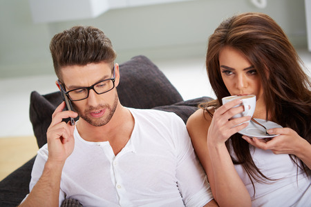 house wife: White Sitting Couple in Casual Clothing Having Coffee, with mobile phone