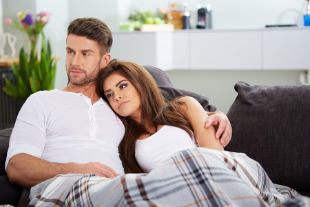 living room boy: Cute couple relaxing on couch at home in the living room