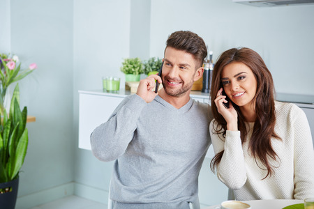 Smiling lovers in front of invoices in house photo