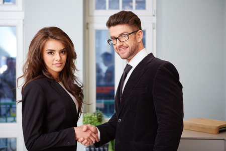 co operation: Businessman And Businesswoman Shaking Hands In Modern Office Stock Photo