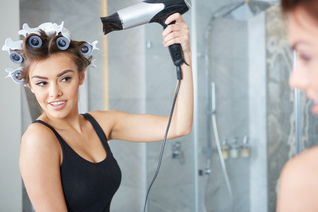 curlers: young woman putting curlers in her hair Stock Photo