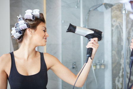 attaches: young woman putting curlers in her hair Stock Photo