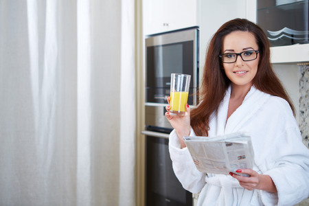 25 29 years: Woman reading the news while drinking orange juice in her kitchen