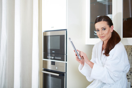 25 29 years: Smiling young woman with tablet in the kitchen