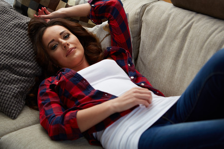good life: Closeup of a smiling young woman lying on couch Stock Photo