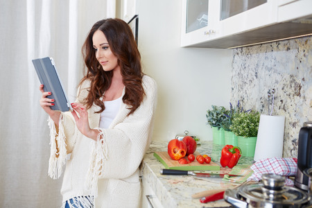 Woman in kitchen looking at recipe on tablet photo
