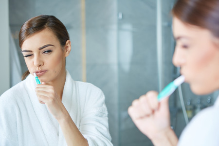 Young pretty woman brushing teeth in front of the mirror