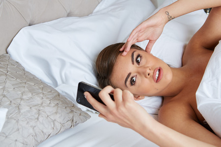 woman laying: Woman lying on bed looking unhappy with a text message