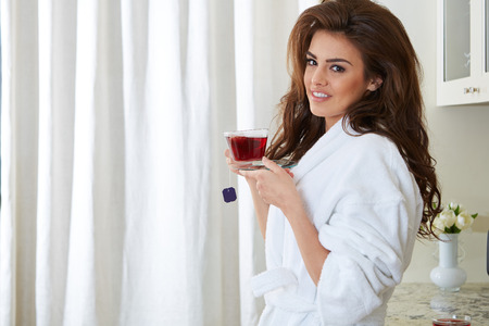 house robes: Young girl with a cup in the kitchen Stock Photo