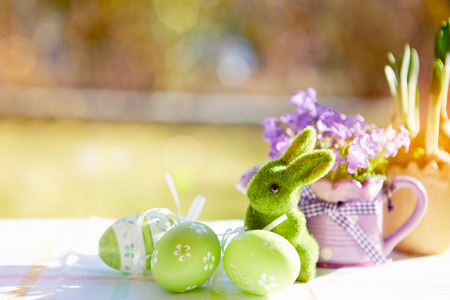 aural: wooden basket with colorful easter eggs and a rabbit on wooden table