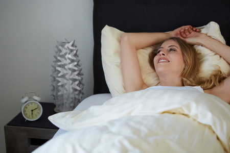 raised viewpoint: attractive woman on the bed in the morning and smiling