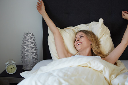 raised viewpoint: attractive woman stretching in the morning and smiling