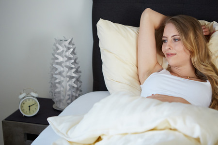 attractive woman on the bed in the morning and smiling photo