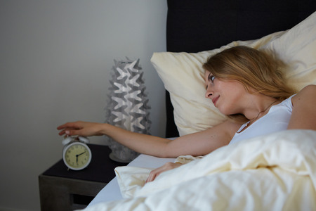 raised viewpoint: attractive woman turn off the alarm clock in the morning Stock Photo